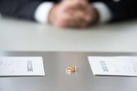 Close up view of decree paper and rings on table as concept of couple divorce, family split up about to sign marriage dissolution document in lawyers office, legal separation settlement concept
