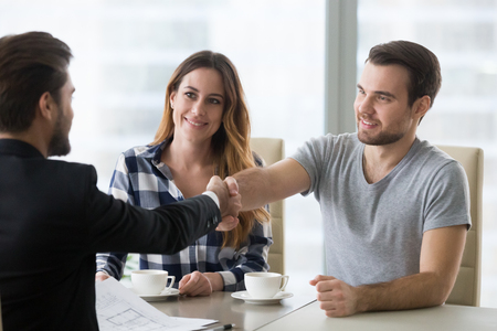 Real estate deal concept, happy couple customers handshaking agent or designer at meeting, satisfied property owners and bank broker shake hands, mortgage loan investment, house purchase