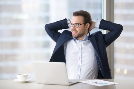 Satisfied successful businessman taking break at workplace to relax finished office work, happy relaxed executive ceo enjoying success feeling relief sitting at work desk, stress free job well done