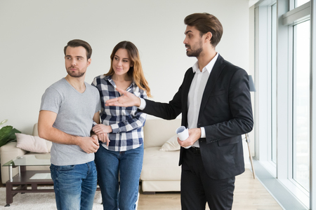 Realtor or landlord showing house apartment to young couple, real estate agent meeting clients consulting customers renters tenants making decision about flat rent viewing rental property for sale Stock Photo