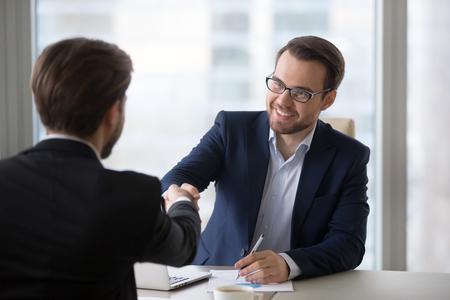 Souriant conseiller en ressources humaines, assureur, directeur de banque, poignée de main, candidat client lors d'une réunion ou d'un entretien d'embauche, des hommes d'affaires satisfaits serrent la main en remerciant pour un bon accord commercial financier, concept d'embauche