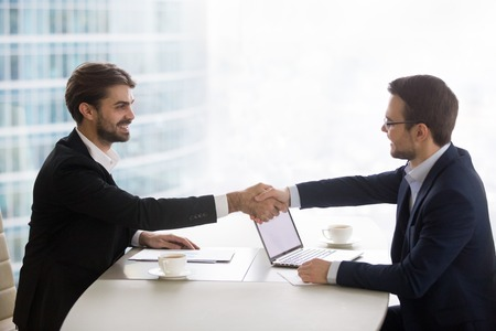 Satisfied happy businessmen in suits shake hands at business corporate office meeting making successful deal concluding contract, male partners manager and client negotiating handshaking, hiring