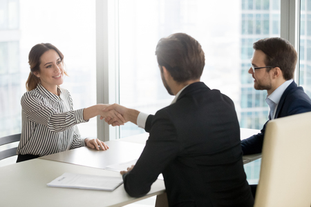 Confident female job applicant shaking hand of hr recruiting manager employer making good first impression starting interview, recruiters congratulate successful vacancy candidate get hired concept