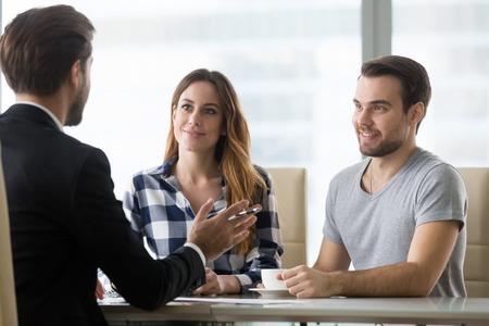 Couple customers consulting lawyer or about buying house or insurance services, salesman, bank worker or financial advisor making presentation offer to clients at meeting in office