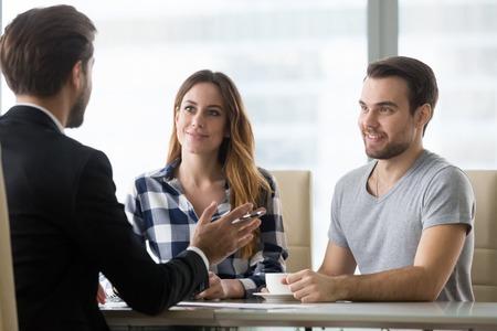 Pareja de clientes consultando a un abogado o sobre la compra de una casa o servicios de seguros, vendedor, trabajador bancario o asesor financiero que hace una oferta de presentación a los clientes en una reunión en la oficina