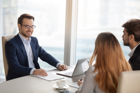 Smiling adviser manager or negotiator consulting business people at meeting, successful businessman negotiating with partners, investor considering deal with clients, corporate executives cooperating