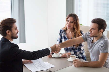 Happy millennial family couple and broker shake hands buying new home or taking mortgage loan investment in bank office, clients handshake real estate agent making property purchase deal