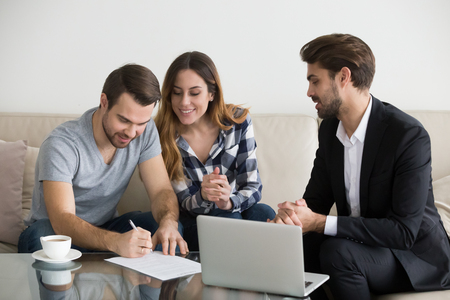 Happy family couple customers renters tenants sign mortgage loan investment agreement or rental sale purchase contract meeting lender or landlord making real estate ownership deal concept. 스톡 콘텐츠