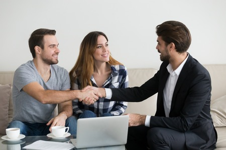 Happy family couple renters tenants handshaking landlord at meeting making real estate deal for apartment rent purchase, clients customers and adviser insurer shake hands, mortgage concept