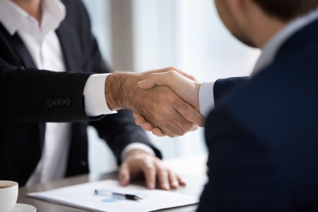 Close up view of male hands shaking at meeting making financial deal, client buying services, corporate partners businessmen supporting union, trust and loyalty with business handshake concept