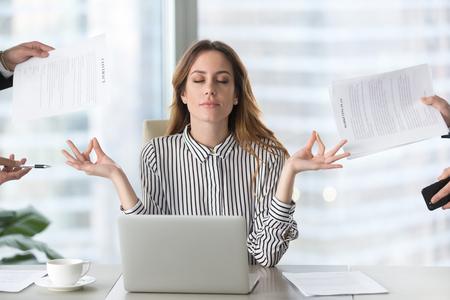 Calma dirigente femminile meditando prendendo una pausa al lavoro per l'equilibrio mentale, consapevole donna d'affari che sente sollievo e senza stress facendo yoga al lavoro ignorando evitando lavoro stressante e scartoffie in ufficio
