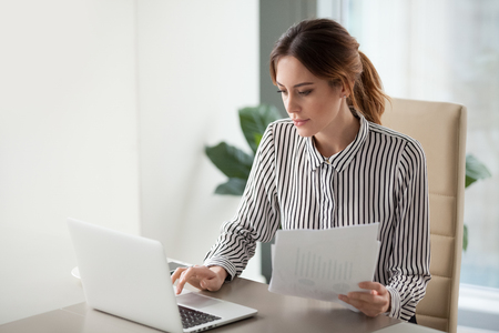 Serious focused businesswoman typing on laptop holding papers preparing report analyzing work results, female executive doing paperwork at workplace using computer online software for data analysis Stock Photo