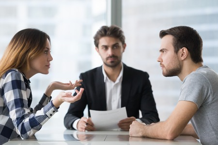 Annoyed unhappy married couple arguing in lawyers office get divorced, angry family spouses split up having disagreement disputing about breaking up and divorce settlement, legal separation concept Фото со стока