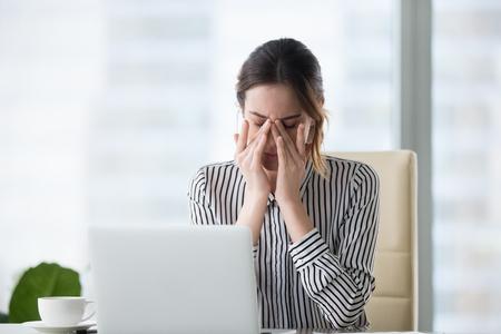 Vermoeide zakenvrouw die ogen masseert, vermoeidheid voelt, hoofdpijn, pijn verlicht, uitgeputte vrouwelijke werknemer die lijdt aan migraine, vermoeide ogen na computerwerk, gezichtsvermogenprobleem, overwerkconcept Stockfoto