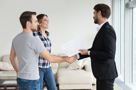 landlord handshaking couple buyers tenants make real estate deal holding rental agreement or sale purchase contract, agent and clients shake hands welcoming renters in new home apartment Standard-Bild - 118204436