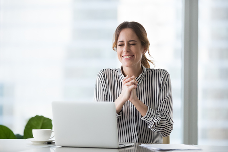 Excited businesswoman wishing for business success or celebrating victory enjoying new opportunity sitting at workplace with laptop, motivated female worker hoping for dream come true feel gratitude