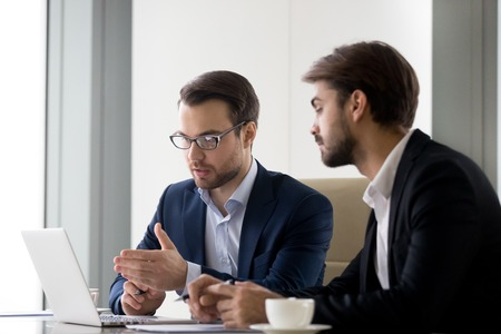 Executive businessmen colleagues working together helping in office teamwork on laptop discuss online project, financial advisor insurer salesman speaking consult client listen computer presentation Banque d'images - 118204449
