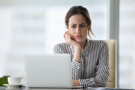 Confused businesswoman annoyed by online problem, spam email or fake internet news looking at laptop, female office worker feeling shocked about stuck computer, bewildered by scam message or virus