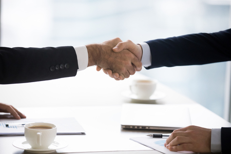 Two male partners shake hands at meeting forming partnership, executive businessmen in suits handshake after successful negotiation closing deal thanking for collaboration help support close up view