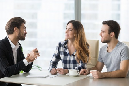 Lawyer, insurer or salesman consulting happy millennial couple making offer, young clients customers planning mortgage loan investment with bank worker, buying services consideration concept