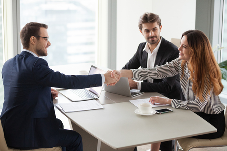 Businessman handshaking businesswoman making deal finishing group negotiations, satisfied smiling business partners conclude contract agreement shake hands expressing respect thank for group meeting Stock Photo