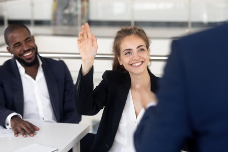 Cheerful young female worker raise hand asking questions coach, multiracial employees or interns gather in seminar for improve knowledge reach success in business sphere. Educational training concept