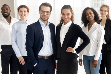 Smiling different ethnicity diverse professionals company members wearing formal clothes posing together looking at camera standing in modern office. Successful team portrait, motivated staff concept