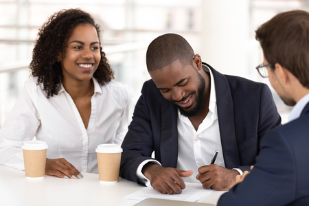 Black satisfied businessman sitting with diverse partners at conference table, signing contract, make purchase and good deal, legalizing cooperation, fill document put signature on legal paper concept