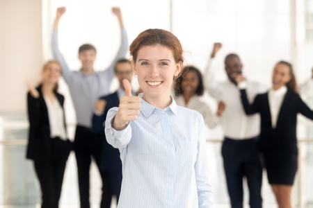 Focus on female client looking at camera show thumbs up satisfied with service, cheerful diverse employees standing on background. Raising finger symbol of best choice approval recommendation concept 写真素材