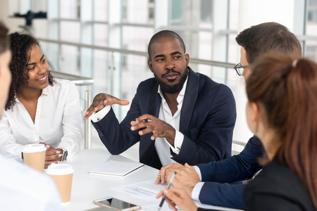 Millennial employees gathered in boardroom for training, black boss ceo leader leading corporate team during seminar learning at modern office. Internship and leadership coaching and education concept Stock Photo