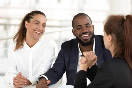Multiracial businesspeople sitting at desk in modern office room, smiling diverse teammates enjoying talk to colleagues during teamwork or friendly hr managers interviewing vacancy candidature concept