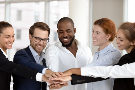 Six multinational millennial happy employees put join hands together in stack pile at group meeting, success celebration, corporate unity, help support promises in teamwork and team building concept Stockfoto