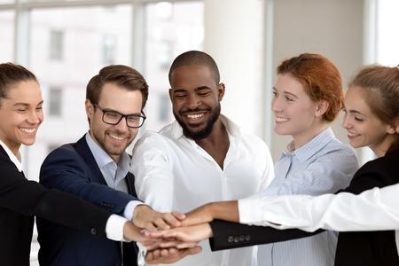 Sześciu międzynarodowych, szczęśliwych pracowników milenijnych łączy ręce w stos na spotkaniu grupowym, celebrowaniu sukcesu, jedności korporacyjnej, pomaga wspierać obietnice w pracy zespołowej i koncepcji budowania zespołu