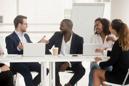 Multiracial millennial employees sitting at boardroom desk listen team leader company executive manager people discuss project plan at group briefing talking at meeting. Teamwork or mentoring concept