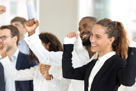 Multi-ethnic happy euphoric business people in formal suits celebrating business success raising hands showing Yes we did it gesture feels overjoyed enjoying great victory. Win and achievement concept