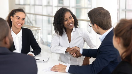 Multiracial businessman businesswoman shake hands starting collaboration at group negotiations, positive people gathered at modern office boardroom, partnership teamwork and business etiquette concept