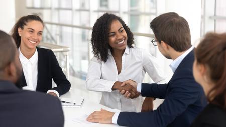 Wielorasowy biznesmen bizneswoman uścisk dłoni, rozpoczynając współpracę podczas negocjacji grupowych, pozytywni ludzie zebrani w sali konferencyjnej nowoczesnego biura, partnerska praca zespołowa i koncepcja etykiety biznesowej