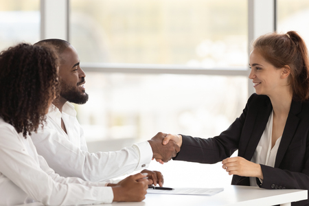 Mixed race black hr manager greeting young caucasian female applicant businesspeople starting job interview. Client and executive managers begin formal negotiations. Human resources and hiring concept