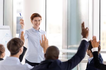 Les hommes d'affaires multiraciaux réunis dans la salle du conseil améliorent leurs connaissances lors d'un séminaire de formation en entreprise, le personnel levant la main votant exprime son opinion à l'unanimité. Idée de soutien et concept de personnes partageant les mêmes idées