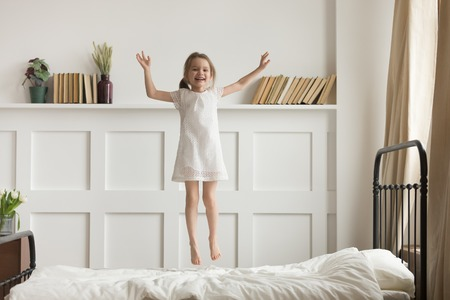 Happy funny little child girl in motion jumping on bed alone flying in air feeling joy, cheerful cute active kid having fun playing laughing in bedroom after waking up, good morning children concept Stockfoto