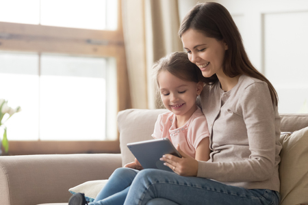 Happy family mom and kid daughter using digital tablet sitting on sofa, smiling parent mother with child girl holding pc computer looking at screen do online shopping make video call watch cartoons