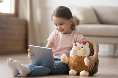 Curious little child girl having fun using digital tablet alone embracing toy sitting on floor, happy preschool smart kid playing with computer looking at screen watching cartoons online at home Stock Photo