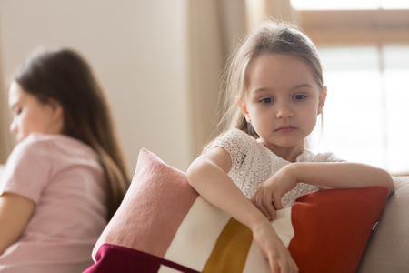 Upset kid daughter sad after family conflict fight with mother feeling lack of love and attention, offended little child girl pouting ignoring mom depressed by punishment in unhappy childhood concept Stock Photo