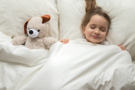 Happy cute baby girl sleeping with teddy bear toy in comfortable bed lay on pillow covered with warm blanket duvet, little kid fall asleep in bedroom, good night healthy child sleep concept, top view Banco de Imagens