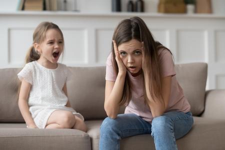 Gestresste, erschöpfte Mutter, die in die Kamera schaut und verzweifelt über schreiende, störrische Tochter-Tochter-Wutanfälle, verärgerte verärgerte Mutter, die müde ist von ungezogenem, schwierigem Kindermädchen, das nach Aufmerksamkeit schreit, verzweifelt ist