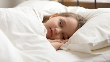 Calm kid girl sleeping well alone on soft pillow covered with warm blanket duvet lying in comfortable bed, cute little child resting asleep on white sheet napping in good night healthy peaceful sleep