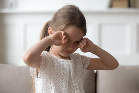 Schläfriges, gestresstes, müdes, verärgertes kleines Kind, das weint, sich die Augen reibt, fühlt sich missbraucht, verletzte Schmerzen, trauriges einsames besorgtes Vorschulkindmädchen in Tränen vermissen die Eltern, die allein auf dem Sofa sitzen, unglückliches Kindergefühlskonzept Standard-Bild