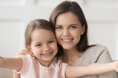 Head shot of happy family single mother elder sister and little kid daughter embracing bonding, young smiling mom posing for portrait with cute child girl hugging looking at camera showing love care