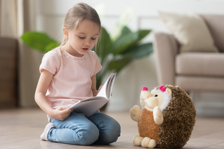 Cute smart little kid girl playing alone reading story to fluffy hedgehog sitting on warm floor at home, funny creative preschool small child holding book teaching toy, children imagination education Фото со стока