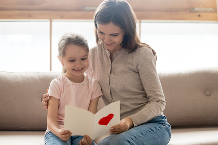 Happy family young mom and little cute kid daughter holding reading greeting card with red heart sitting on sofa at home, child girl congratulating mum with birthday mothers day making gift present Stockfoto